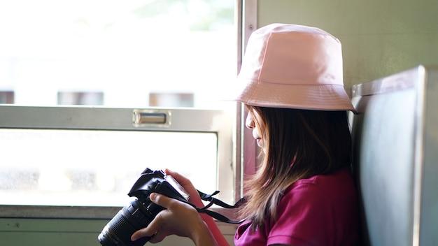 電車の中で写真を撮るアジアの女性