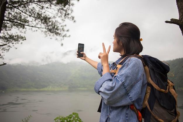 호수 숲에서 자화상 사진을 복용하는 아시아 여자