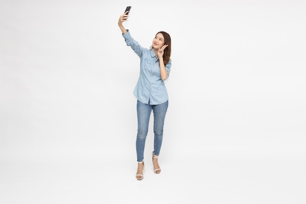 Asian woman taking a selfie by mobile phone isolated over white background