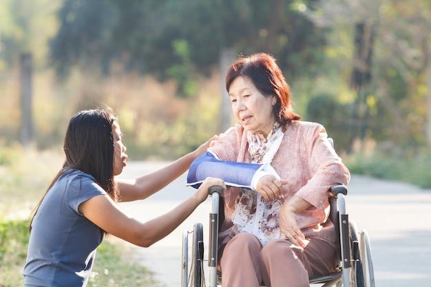 タイの公園で散歩のために彼らの障害のある年配の母親を連れて行くアジアの女性