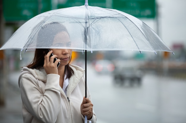 Asian woman talking on a cell phone and holding umbrella while standing on the city street in the rainy day.