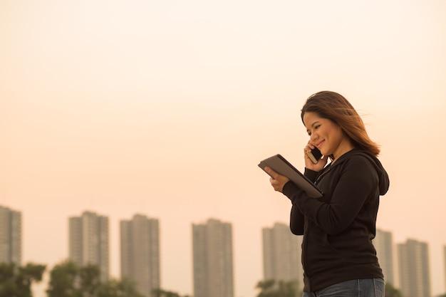 일몰 하늘을 배경으로 태블릿을 들고 휴대전화로 통화하는 아시아 여성