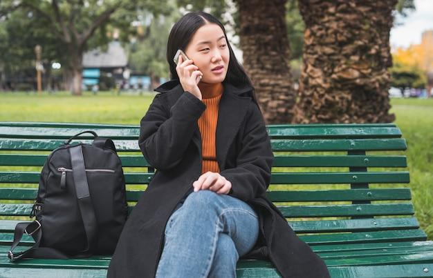アジアの女性が電話で話しています。