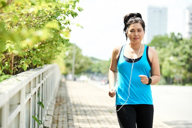 Asian woman in tank top and leggings, with earphones, jogging in morning in urban street