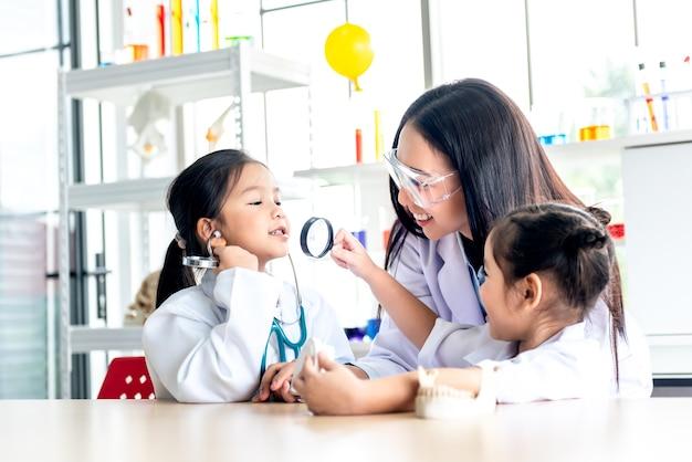 과학에서 흰색 의사 유니폼을 입고 아시아 여자 교사와 2 여자 학생
