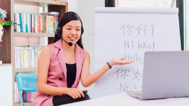 Азиатская женщина-учитель преподает удаленно в домашнем офисе с онлайн-технологией ноутбука.