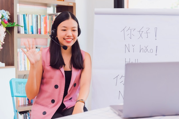 Asian woman teacher teaching remotely at home office with online technology laptop.