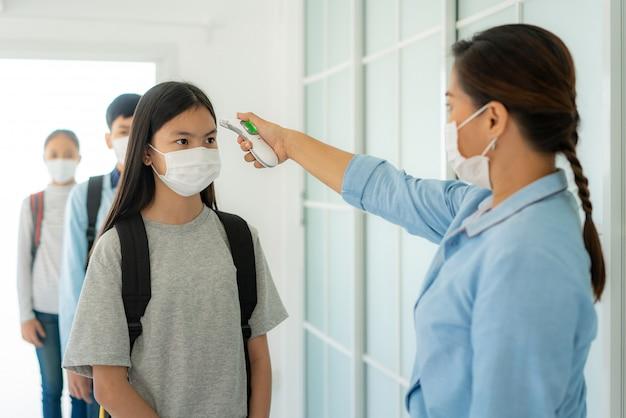温度計を使用して学生をチェックするアジアの女性教師