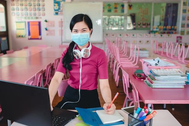 Азиатская женщина-учитель в медицинских масках обучает учащихся детских садов в режиме онлайн. преподаватели и учащиеся используют системы онлайн-видеоконференций для обучения учащихся.