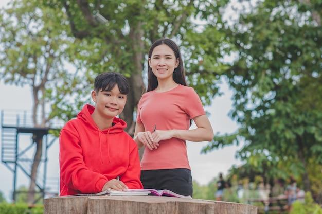 学生の少年を教えるアジアの女性