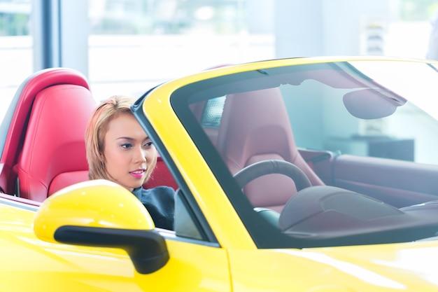Азиатская женщина тестирует новый спортивный автомобиль
