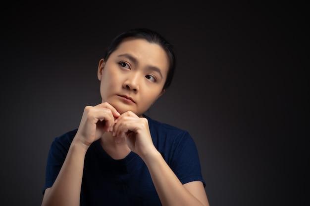 Азиатская женщина думает о проблеме, обеспокоенной и запутанной эмоции, изолированной на фоне.