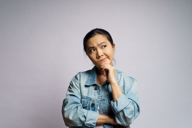 Asian woman thinking about problem, worried and confused emotion isolated