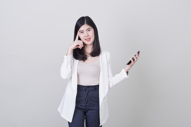 Asian woman thinking holding mobile phone