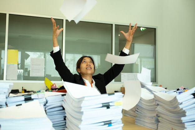 Asian woman throwing paper documents while working on project in office.