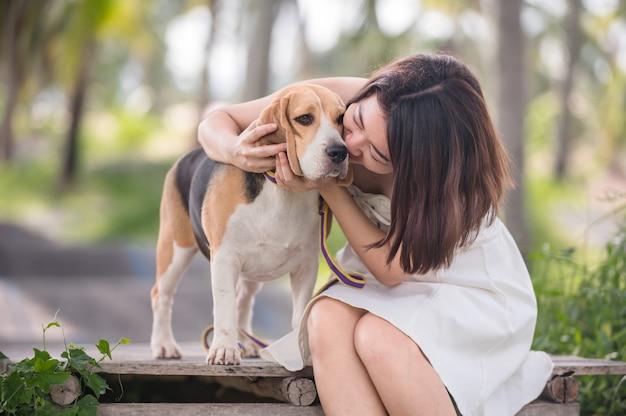 Азиатская женщина вместе с собакой как лучший друг. соло на открытом воздухе в парке.