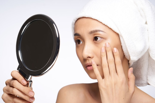 Asian woman touching hand face mirror in hands skin care