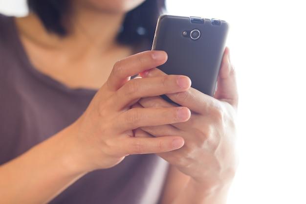 スマートフォン、明るい背景、クローズアップに触れるアジアの女性。