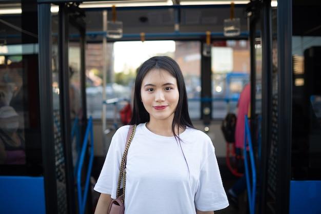 아시아 여성 관광객은 대중 교통 정류장 버스 또는 트램을 탄 후 문을 통해 나옵니다.