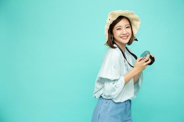 Азиатская женщина-турист, держащая цифровую камеру изолирована