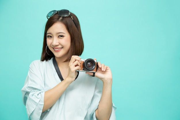 Asian woman tourist holding digital camera isolated