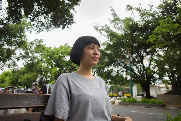 アジアの女性観光客が街の通りに屋外で一人で休日を旅行して笑っている