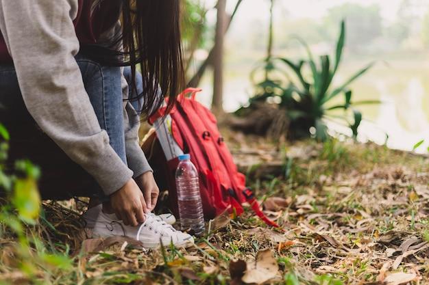 Asian woman tourist tie shoelaces.