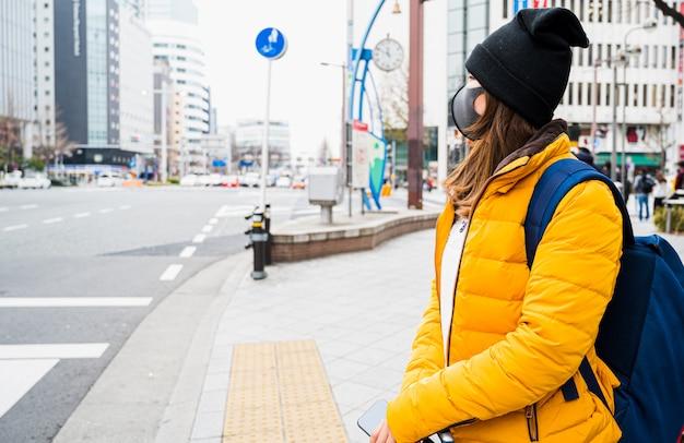 アジアの女性観光客は、フェイスマスクを身に着けて日本を旅行します。コロナウイルスインフルエンザウイルス旅行の概念