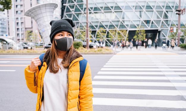 アジアの女性観光客は、フェイスマスクを身に着けて日本を旅行します。コロナウイルスインフルエンザ