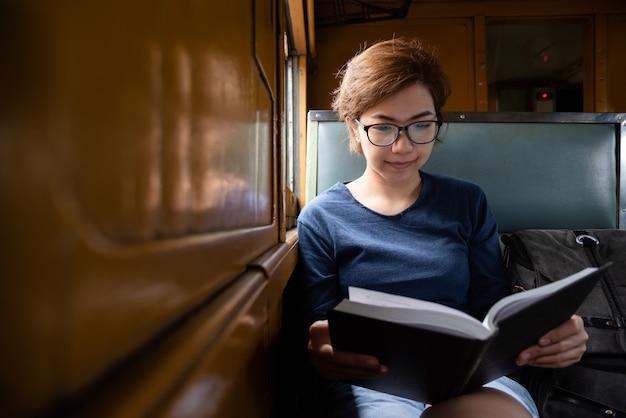 アジアの女性観光客が眼鏡をかけて電車の中で本を読んでいます。