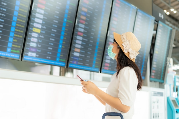 空港ターミナルの到着出発ボードからフライトをチェックするフェイスマスクを着ているアジアの女性観光客