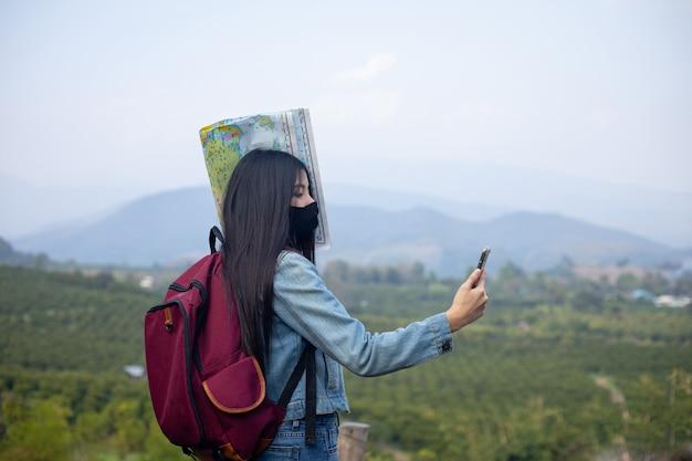 Азиатская женщина турист в маске для лица, глядя на телефон