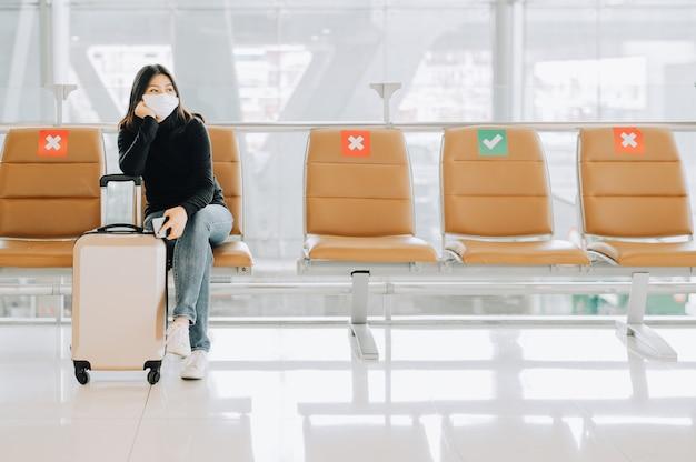 코로나 바이러스 또는 covid-19 발발 중 비행기를 기다리는 수하물과 함께 사회적 거리 의자에 앉아 얼굴 마스크를 착용하는 아시아 여성 관광객. 새로운 일반 여행 컨셉