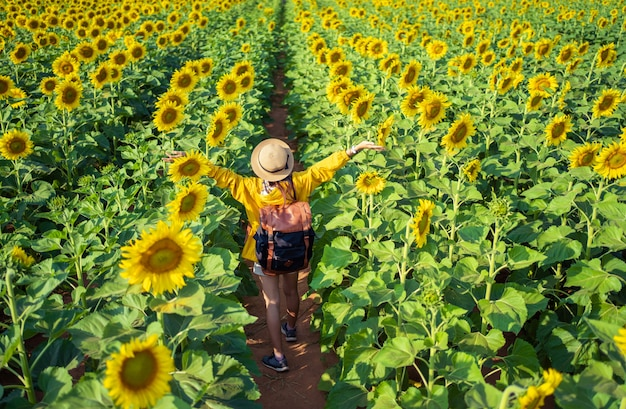 Asian woman tourists she felt relaxed in the sunflower field.