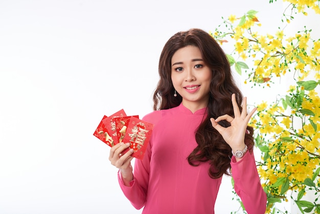 Asian woman in traditional dress gesturing to greet happy holidays