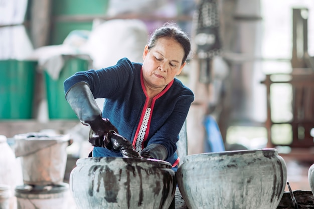 Asian woman in traditional dress indigo dyeing before being woven into fabric which is a product which has built a reputation for sakon nakhon province, thailand.