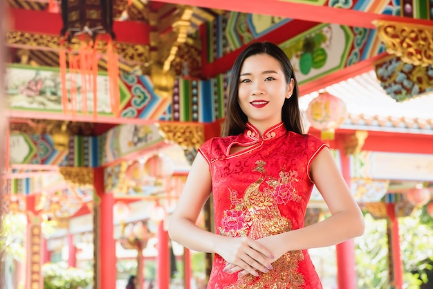 Asian woman in traditional red cheongsam qipao dress
