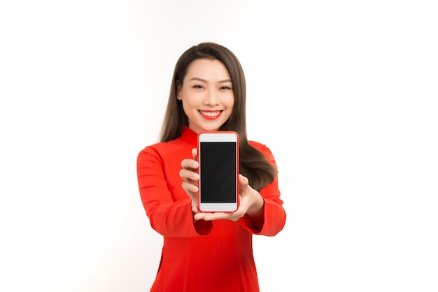 Asian woman in traditional vietnamese dress, presenting mobile screen or application for digital business and technology concept