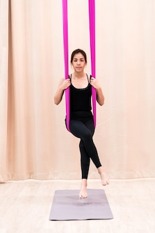 Asian woman training in fitness room with fly yoga elements