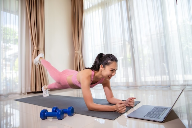 Asian woman training at home, doing plank and watching videos on laptop
