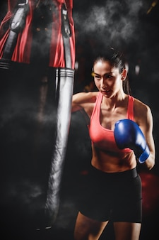 Asian woman training with punching bag in gym