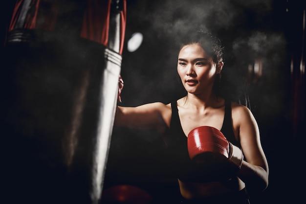 アジアの女性のボクシングジムでサンドバッグでトレーニング