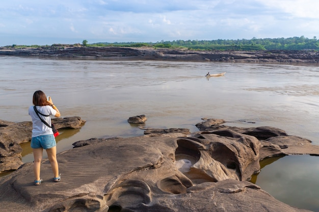 Asian woman travel use smartphone take photo of river and boat at sam pan bok  rock landscape
