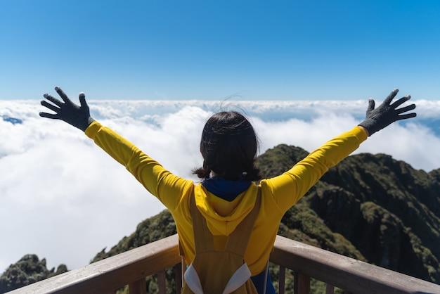 黄色のセーターを着たアジアの女性旅行者は、休暇に丘、雲、空に腕を上げて立っています。