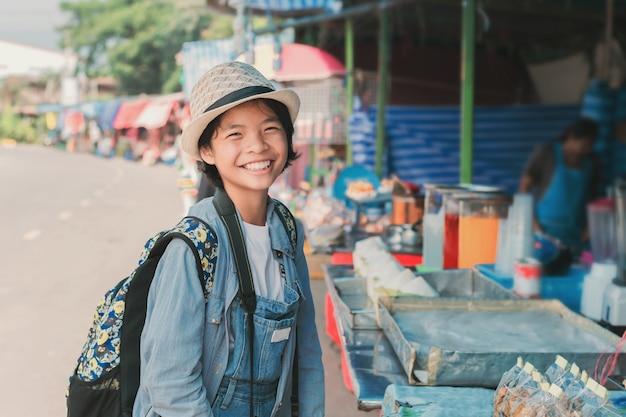 Азиатская женщина-путешественница, идущая по уличному рынку