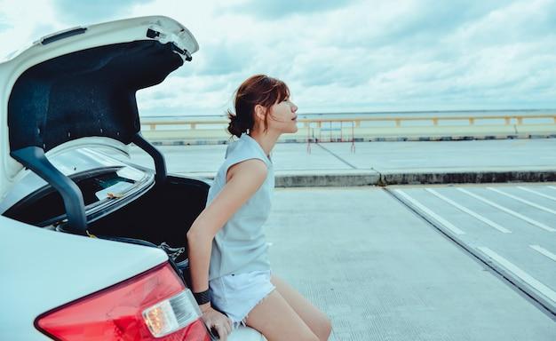 하늘과 도로를 배경으로 해치백 자동차에 앉아 있는 아시아 여성 여행자