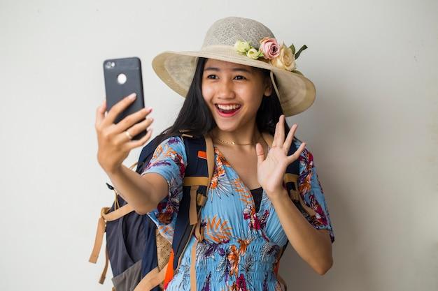 携帯電話で話すアジアの女性旅行者。白い背景の上の夏の旅行の概念