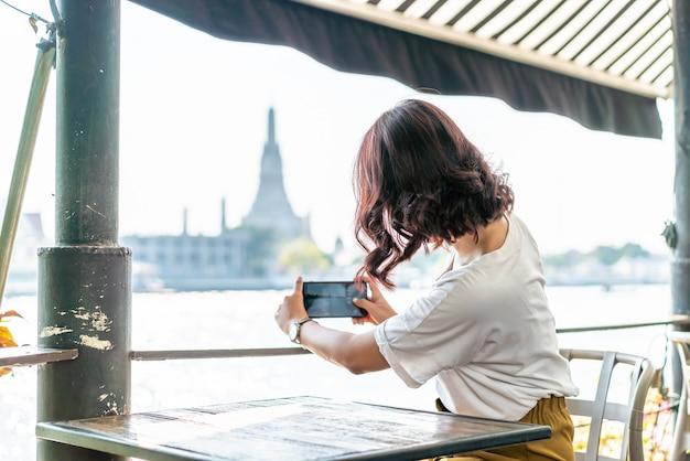 Азиатская женщина путешественник фотографировать в кафе