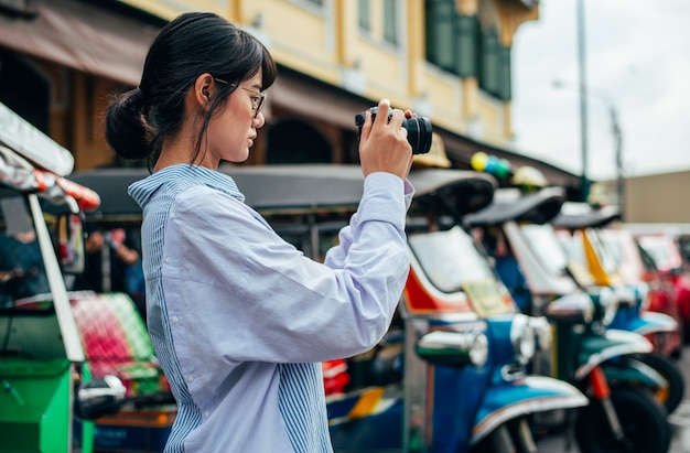 Asian woman traveler uses digital camera takes photo with colorful tuk tuks car background