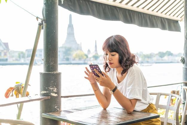 Азиатский путешественник женщины используя ее телефон в кафе